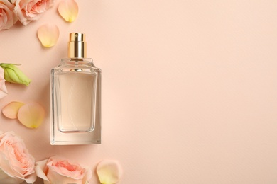 Bottle of perfume, beautiful flowers and petals on beige background, flat lay. Space for text