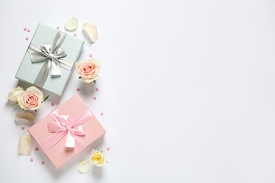 Elegant gift boxes and beautiful flowers on white background, flat lay. Space for text