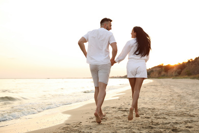 Lovely couple running together on beach at sunset, back view