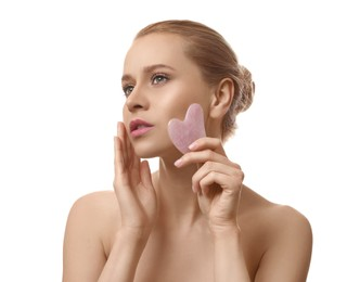 Beautiful young woman doing facial massage with gua sha tool on white background