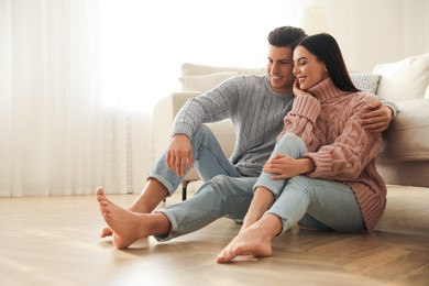Happy couple sitting on warm floor in living room. Heating system