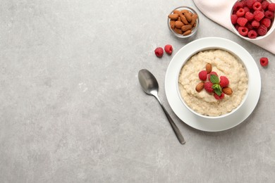 Tasty oatmeal porridge with raspberries and almond nuts served on light grey table, flat lay. Space for text
