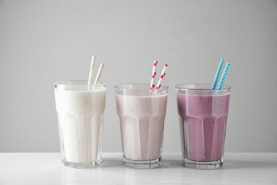 Different tasty milk shakes in glasses on white table