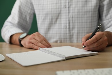 Left-handed man writing in notebook at wooden table, closeup