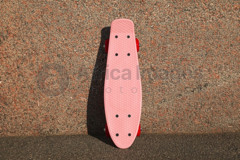 Pink skateboard with red wheels near wall outdoors