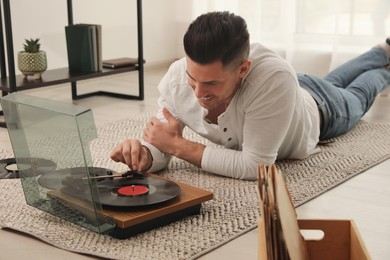 Happy man using turntable while lying on floor at home