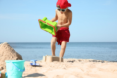 Cute little child playing with plastic toys at sandy beach on sunny day
