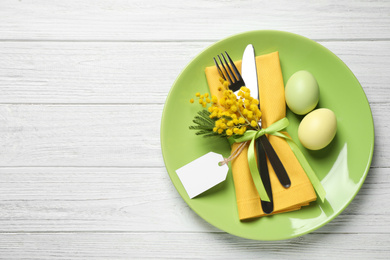 Festive Easter table setting with eggs and floral decor on white wooden background, top view. Space for text