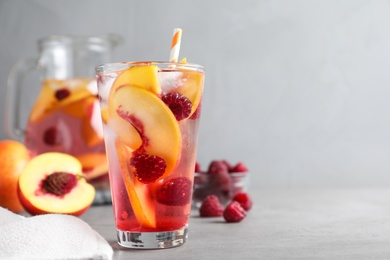 Delicious peach lemonade with soda water and raspberries on grey table, space for text. Fresh summer cocktail
