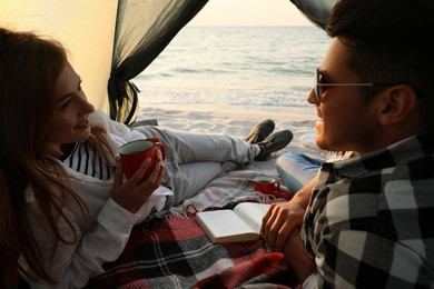 Couple resting in camping tent near sea