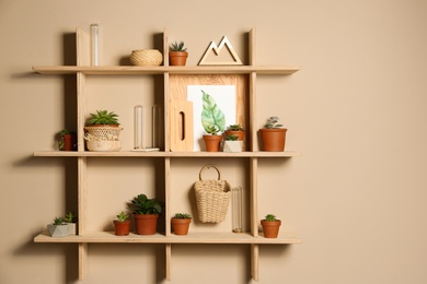 Wooden shelves with different decorative elements on beige wall, space for text