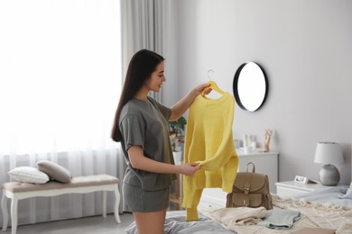 Young woman choosing clothes for work day at home. Morning routine