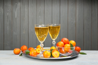 Delicious plum liquor and ripe fruits on table against grey background. Homemade strong alcoholic beverage