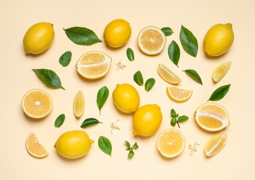 Many fresh ripe lemons with green leaves and flowers on beige background, flat lay