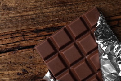 Tasty milk chocolate bar wrapped in foil on wooden table, top view