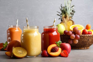 Delicious juices and fresh ingredients on grey table