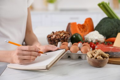 Woman with notebook and healthy food at white table, closeup. Keto diet