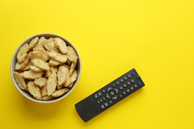 Remote control and rusks on yellow background, flat lay