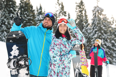 Happy couple with equipment at ski resort. Winter vacation