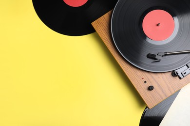 Modern player and vinyl records on yellow background, flat lay. Space for text