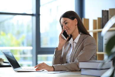 Female business trainer talking on phone while working with laptop in office