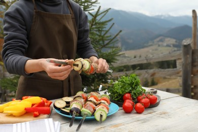 Woman stringing marinated meat and vegetables on skewer at wooden table against mountain landscape, closeup