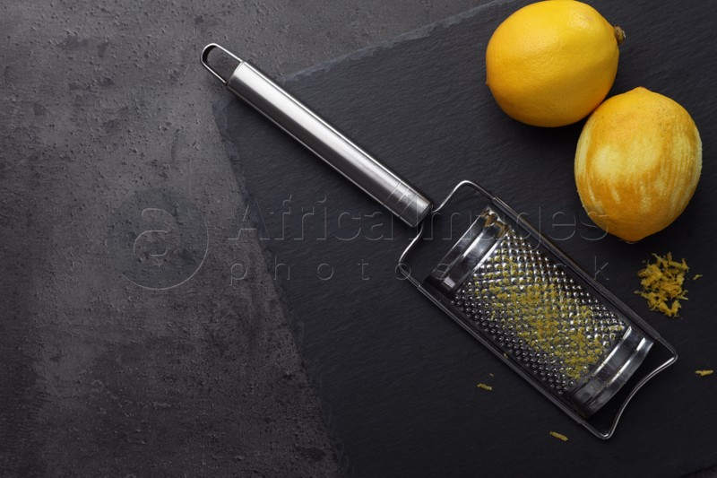 Grater and fresh lemons on black table, flat lay. Space for text