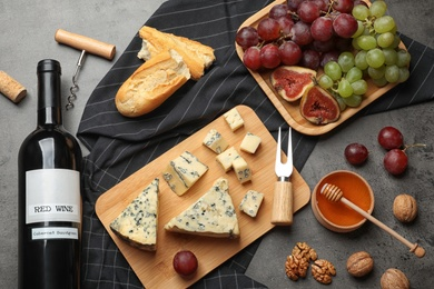 FLat lay composition with board of delicious blue cheese and wine on stone background
