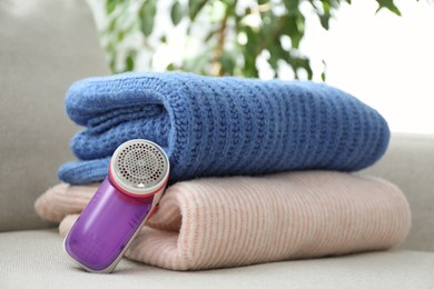 Modern fabric shaver and woolen sweaters on sofa indoors, closeup