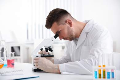 Scientist using modern microscope at table. Medical research
