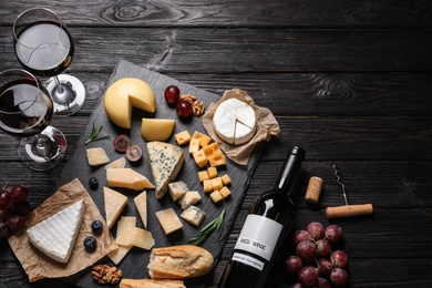 Different types of delicious cheese served on black wooden table, top view