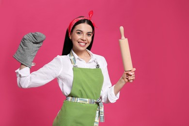 Young housewife in oven glove holding rolling pin on pink background. Space for text
