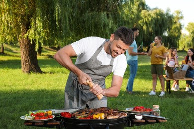 Man cooking meat and vegetables on barbecue grill in park