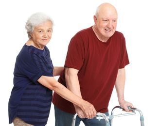 Elderly woman helping her husband with walking frame on white background