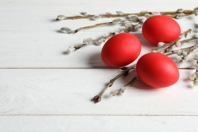 Red dyed Easter eggs and pussy willow on wooden table, space for text