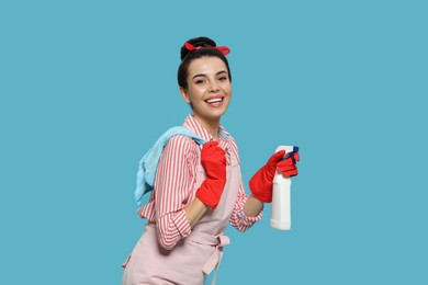 Young housewife with detergent and rug on light blue background