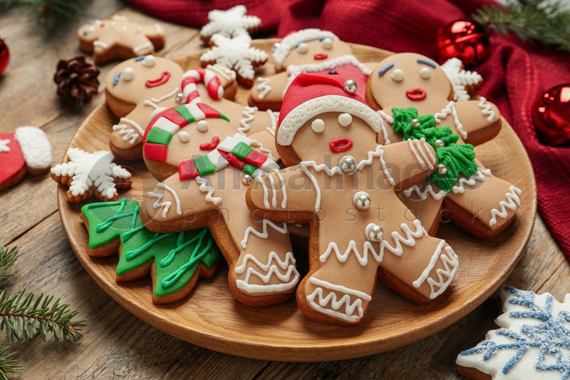 Delicious Christmas cookies and festive decor on wooden table, closeup
