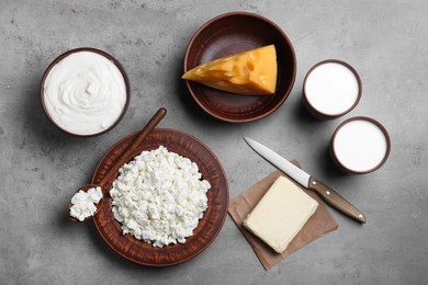 Clay dishware with fresh dairy products on grey table, flat lay
