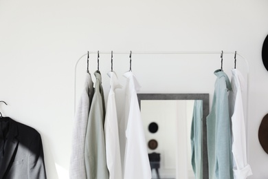 Rack with stylish clothes near mirror in dressing room