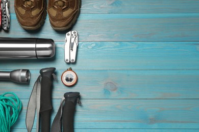 Flat lay composition with trekking poles and other hiking equipment on light blue wooden background, space for text