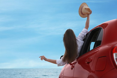 Happy woman leaning out of car window on beach, space for text. Summer vacation trip