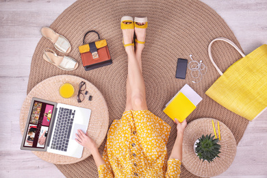 Fashion blogger with laptop sitting on floor, top view