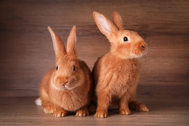 Cute bunnies on table against wooden background. Easter symbol