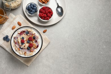 Tasty oatmeal porridge with toppings served on grey table, flat lay. Space for text