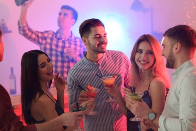Group of young people holding martini cocktails at party