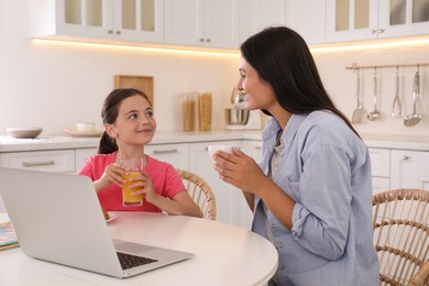 Happy mother and daughter with laptop in kitchen. Single parenting