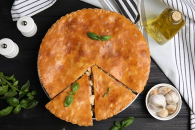 Delicious meat pie served on black wooden table, flat lay