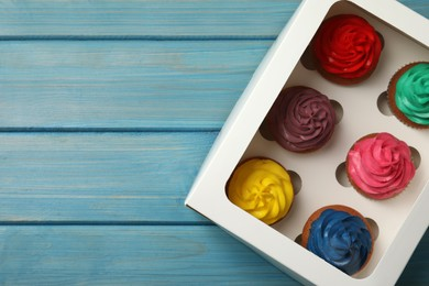 Box with different cupcakes on light blue wooden table, top view. Space for text