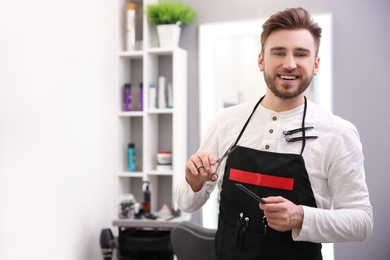 Professional male hairdresser with comb and scissors in salon