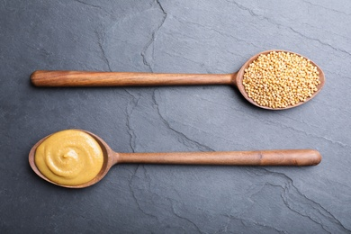 Mustard seeds and sauce in wooden spoons on grey table, flat lay